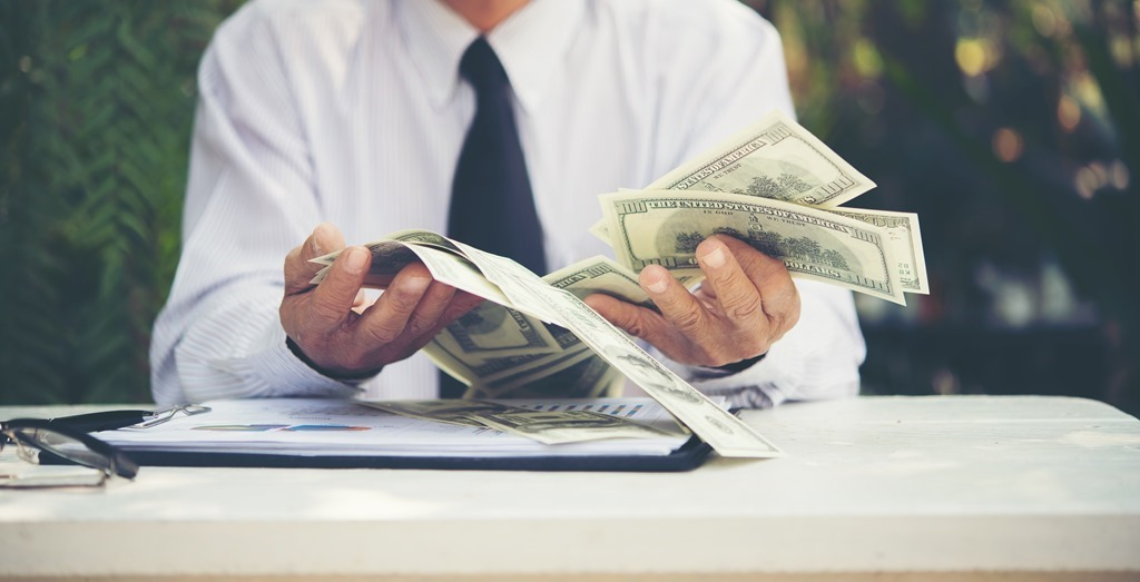 Senior businessman counting U.S. dollar bills.